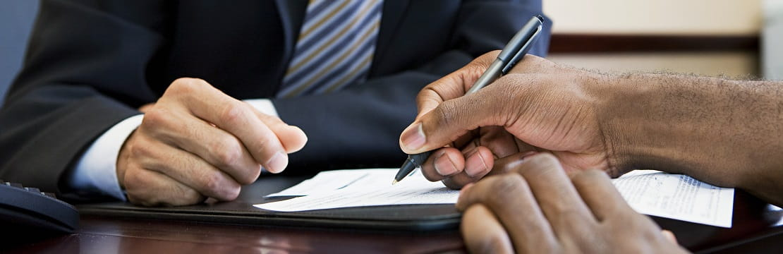 A close-up shot of the hands of two people seated across from one another a desk. One individual holds a pen above a business document.